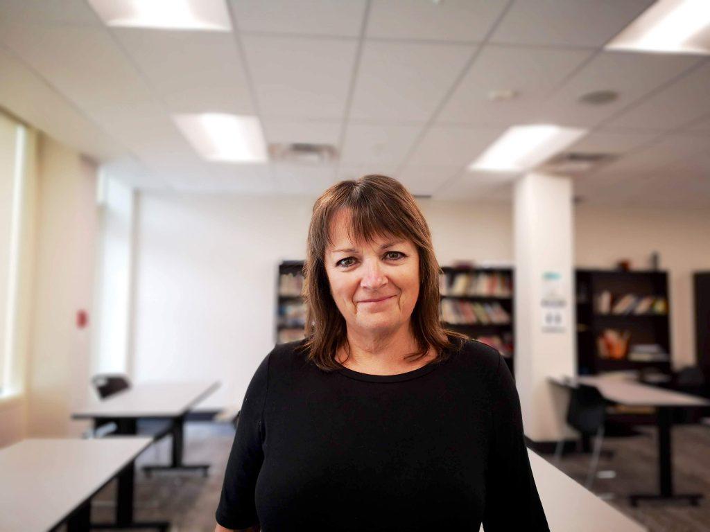 Shauna MacKinnon stands in a classroom.